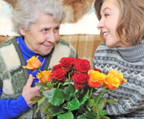 elderly woman and her caregiver with flowers